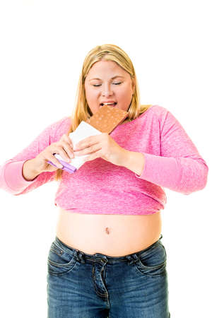 Three quarter body portrait of overweight woman eating large chocolate bar