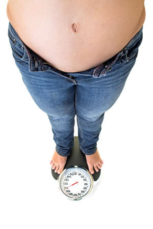 glandular: view from the top of the bare belly of a fat overweight woman standing on a bathroom scale looking down towards her bare feet isolated on white