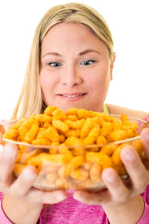 Portrait of smiling young woman with bowl of unhealthy crisps Stock fotó