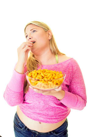Overweight young woman eating from bowl of crisps on white