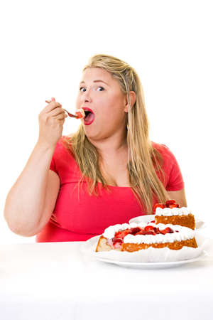 woman eating cake: Overweight young blond woman eating strawberry cream cake on white Stock Photo