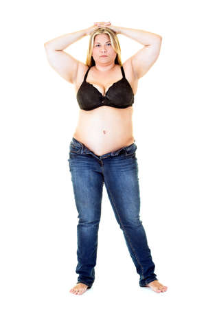 glandular: Overweight young woman full length in bra and jeans with hands on head