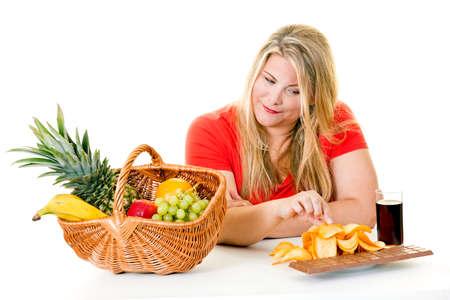 Woman blond woman choosing junk food over basket of healthy fruit on white.