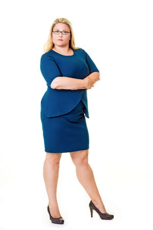 Beautiful plus sized woman in blue dress with arms crossed and staring at the camera.