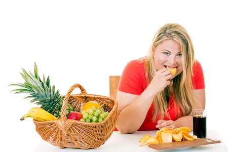 Femme blonde en excès de poids choisissant de manger de la malbouffe plutôt que du panier de fruits sur le blanc.