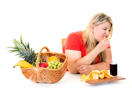 munching: Overweight young woman eating junk food and ignoring basket of healthy fruit  diet concept on white. Stock Photo