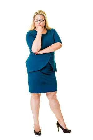 introspective: Thoughtful blond executive in blue dress and black heels with one hand under her chin.