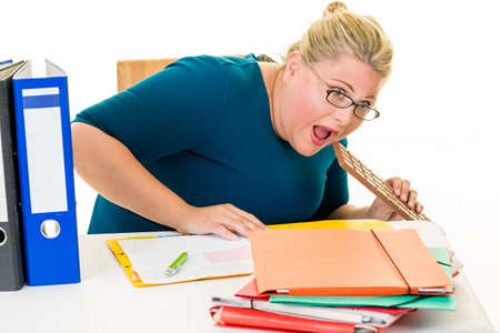 agachado: Overweight young businesswoman at desk eating chocolate bar sneakily on white. Foto de archivo