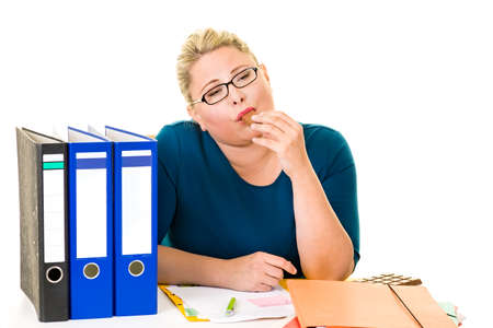Overweight businesswoman at desk enjoying eating chocolate on white. Stock Photo