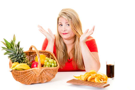 Unsure overweight woman sat between basket of fruit and unhealthy snacks.