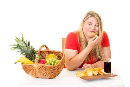 Unhealthy overweight young blond woman eating junk food rather than fruit on white.