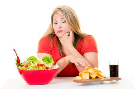 Young woman with choice of salad and junk food looking at bowl on white. Stock Photo