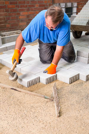 aligning: Contractor or builder installing paving stones on a building site tamping a stone into position with a heavy mallet