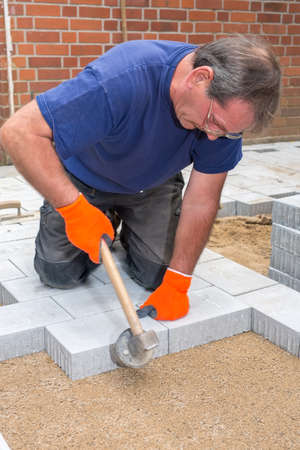 Builder or contractor laying paving stones around a new house tamping them into position using a heavy mallet on a prepared sand base Stock Photo