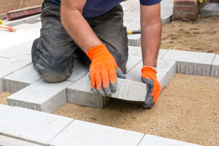 placing: Hands of a builder laying new paving stones carefully placing one in position on a levelled and raked soil base Stock Photo