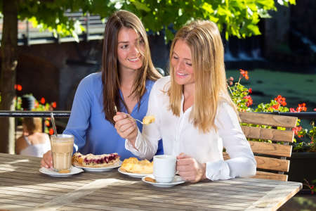 Young pretty brunette woman in blue blouse watching her female friend with blonde hair eating cake and smiling, sitting at street cafe table in sunny day Stock Photo