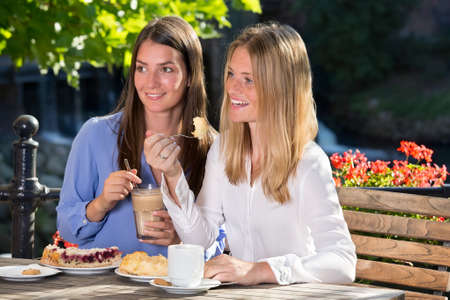 camaraderie: Two beautiful young women in blue and white blouse sitting close together in outdoor cafe or terrace, looking away at something and smiling, while eating desserts with coffee Stock Photo