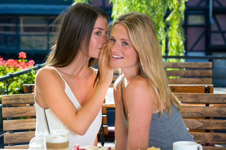 Young beautiful brunette woman whispering a secret into her blonde friend ear, sitting in street cafe in sunny day. Girls are smiling and looking away