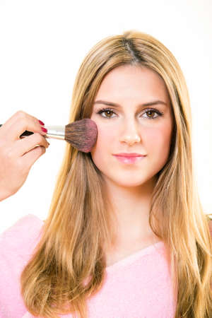 Pink blusher being applied to contour a cheek of a pretty young blond woman using a large soft bristle cosmetics brush in a beauty and fashion concept isolated on white Stock Photo