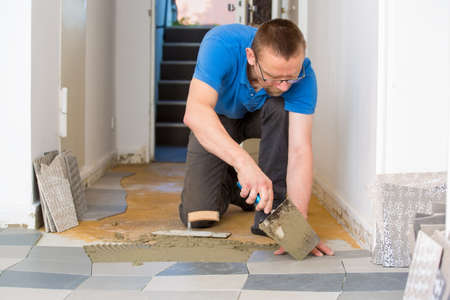 Man Tiling Floor In New House Using Trowel Stock Photo Picture And