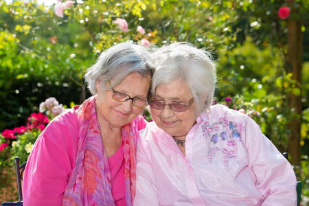 Two smiling senior women sitting together in garden on sunny day