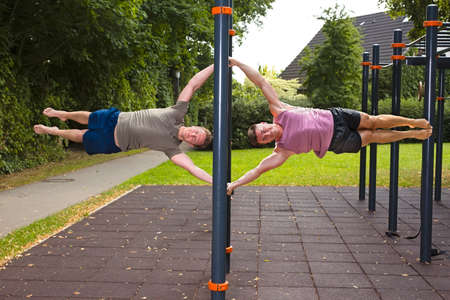 Young athletes showing human flag, during street workout for body mastery outdoors on a summer day.