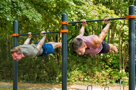 Young athletes hanging belly-down parallel to the ground, back lever workout on horizontal bar for body mastery on sunny day in summer. 写真素材