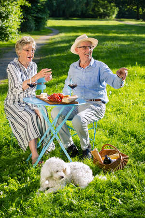 Two family members laughing heartily as they look and pointing at something off screen to the right from picnic table, cute white dog looking at same direction.