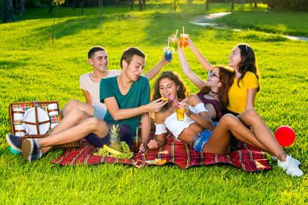 Cheerful young people drinking cocktails on picnic party, sitting and laying on red rug on green lawn, viewed from high angle. Guy sharing a bite of snack with his beautiful girl friend.