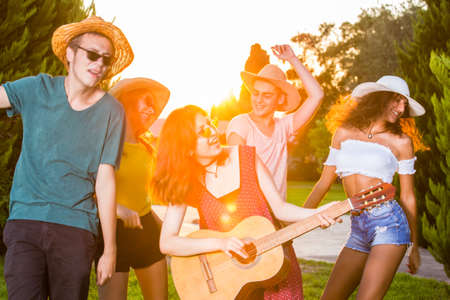 Group of happy young friends singing and dancing, enjoying summer in park. Front half-length portrait of a girl playing guitar, dancing and smiling.