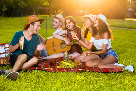 Group of young friends musicians on picnic party, sitting together on red rug in park, playing guitar and laughing.