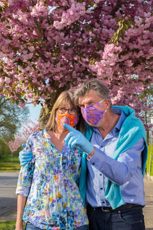Affectionate senior couple wearing colorful face masks and gloves during the coronavirus pandemic standing arm in arm having a discussion and pointing in front of a tree with pink spring blossom. Banque d'images