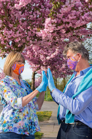 Senior couple wearing protective face masks and gloves giving a high fives as they celebrate their good health during the coronavirus pandemic under pink spring blossom outdoors.