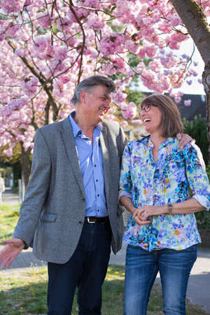 Fun loving senior couple enjoying a joke standing together under a tree with pink spring blossom laughing together.