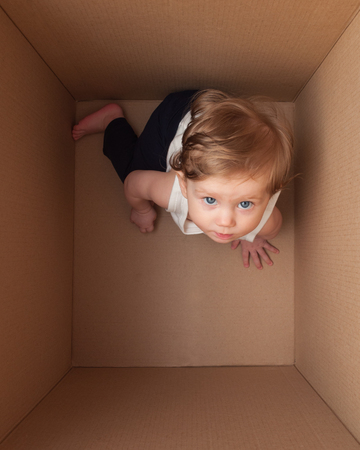 Child inside cardboard package box.
