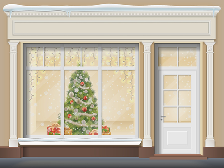 The storefront is with a door and a large window. Christmas showcase decorated with a xmas tree, glowing garland, snowflakes and gift boxes.