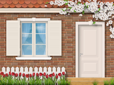 The facade of a country house in the spring. Brick wall with window and door. In the front garden grow red tulips.