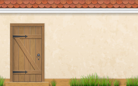 Stucco wall of a house with an old wooden door. Fence and grass in a front garden.