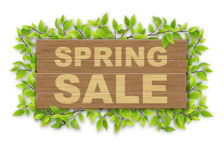 Wooden sign with spring sale text on a background of tree branches with green leaves. Banner or an advertisement for a seasonal discount.
