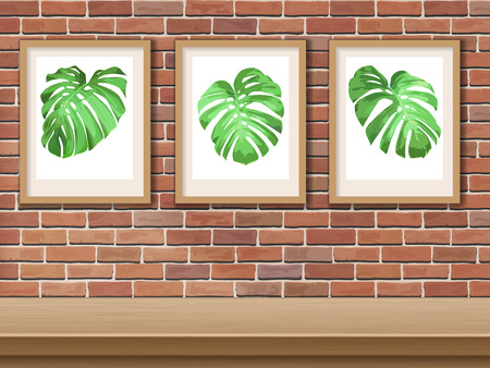 Framed picture with monstera leaf on brick wall background.