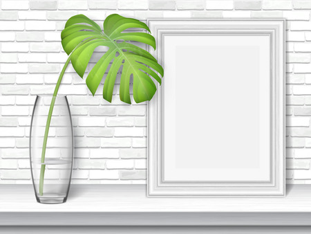Monstera leaf and picture frame on a white table on brick wall background.