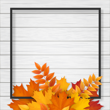 Black frame with autumn fallen leaves on white wooden background. Background for seasonal sale offer or design element banner.