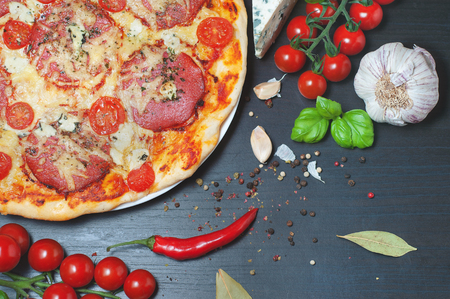 Pizza and vegetables on a dark wooden table. Ingredients for pizza on a black