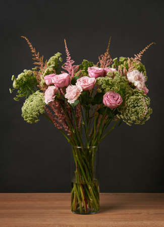 Beautiful bouquet of flowers peony rose, ammi, astilbe, carnation on a dark background.