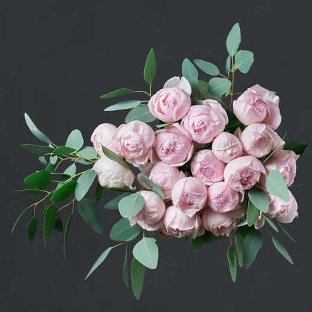 Beautiful bouquet of flowers with pink roses, black hydrangea and green eucalyptus leaves. Dark background. Top view