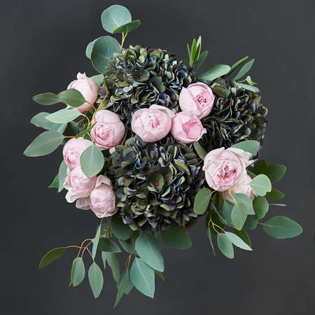 Beautiful bouquet of flowers with pink roses, black hydrangea and green eucalyptus leaves. Dark background. Top view Banco de Imagens - 155486017