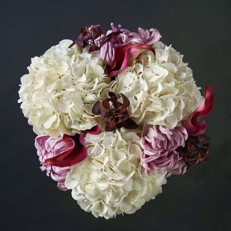 Autumn bouquet of white hydrangea, red calla and pink chrysanthemum. Background for a greeting card. Dark background. Top view.