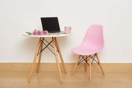 A pink chair and a white table against the wall. On the table are a laptop, glasses, a cup and a bouquet of roses. Studio interior or workplace.
