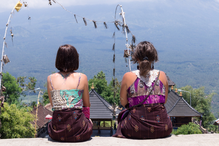 Young caucasian women tourist near the balinese hindu temple. The volcano Agung on the background. Rare view.