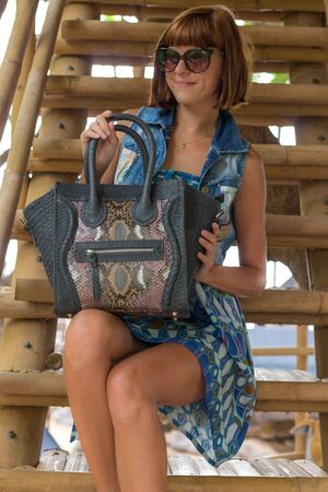 bodyscape: Fashion portrait of pretty young caucasian woman with handmade snakeskin python handbag. Sunny day on a tropical Bali island. Stock Photo